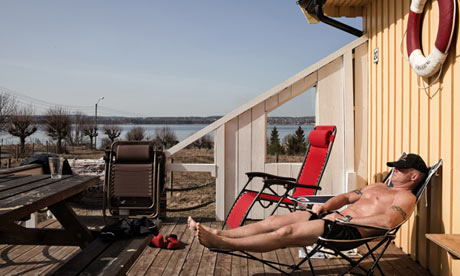 """An inmate sunbathes on the deck of his bungalow on Bastoy."" Photograph: Marco Di LauroSource: The Guardian"