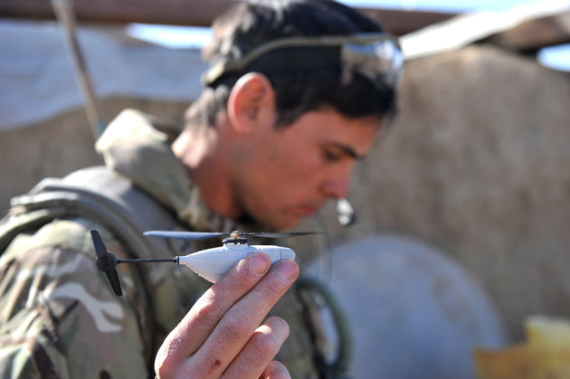 """Associated Press/ Sgt Ruper Frere - Undated image released by the British Army Monday Feb 4 2013 of Sergeant Scott Weaver, of The Queens Royal Lancers launching a newly issued Black Hornet miniature surveillance helicopter during an operation in Afghanistan. The Scandinavian-designed Black Hornet Nano weighs as little as 16 grams (0.56 ounces) — the same as a finch. The four-inch-long (10-centimeter-long) helicopter is fitted with a tiny camera which relays still images and video to a remote terminal. Troops used the drone to look for insurgent firing points and check out exposed areas of the ground before crossing. ""(AP Photo/ Sgt Ruper Frere)"