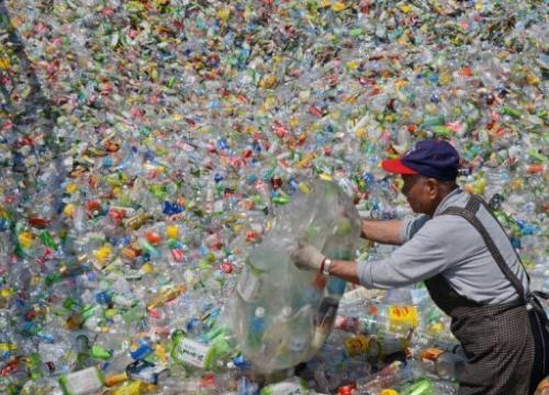 """A volunteer of the Taiwan Buddhist Tzu Chi Foundation sorts through plastic bottles at a recycling plant in Taipei on February 28, 2013. Tzu Chi runs 5,400 recycling stations across Taiwan with the help of more than 76,000 volunteers.""-Source: Physics.org"