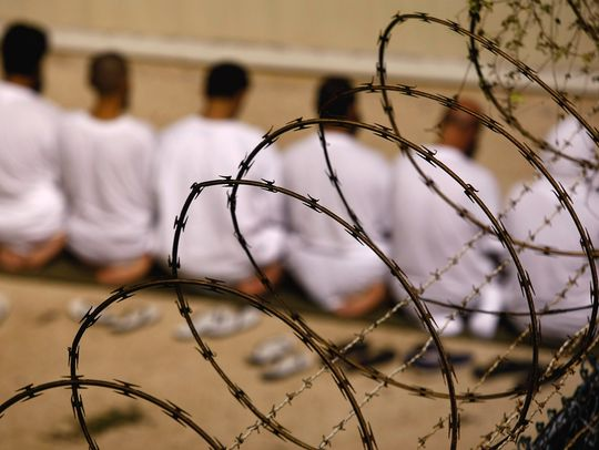 """Detainees kneel during an early morning Islamic prayer at the U.S. military prison for enemy combatants at Guantanamo Bay, Cuba, in 2009.""  (Photo: John Moore, Getty Images)  Source: USAToday"